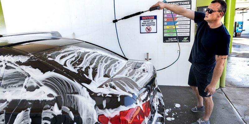 Happy Hoppy's customer using the high pressure water hose in one of the DIY car wash Brisbane serve bays
