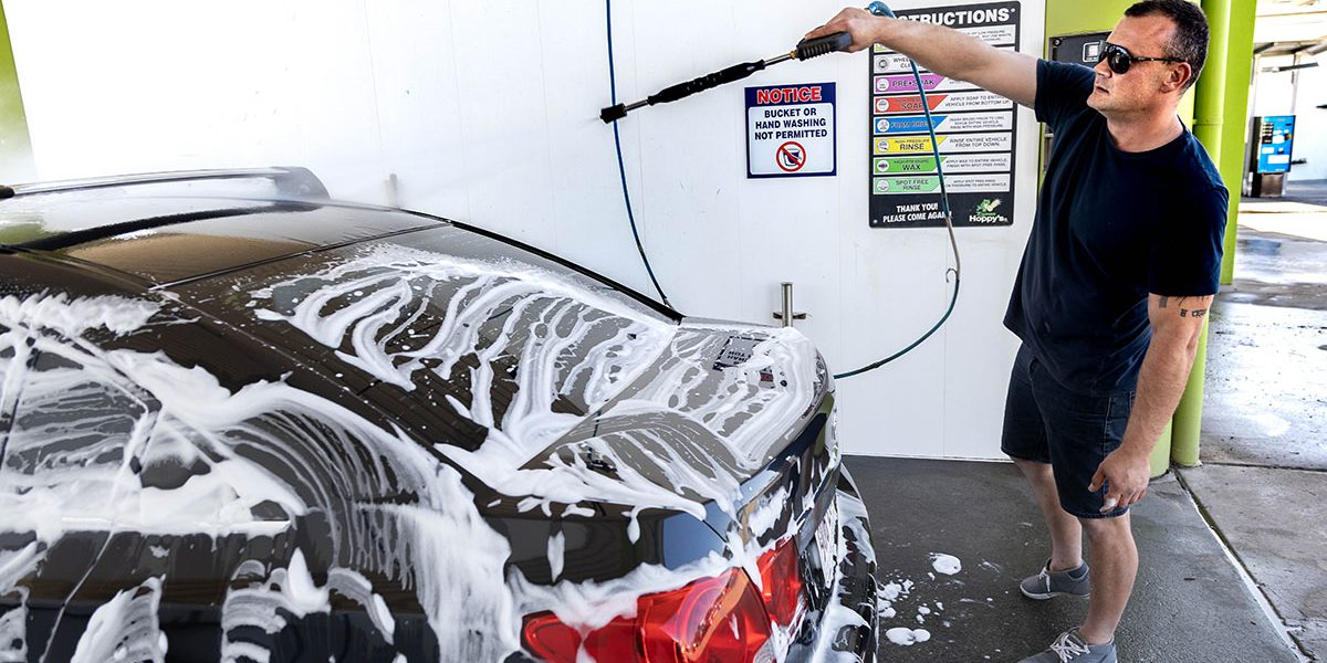 Happy Hoppy's customer using the high pressure water hose in one of the DIY car wash Brisbane serve bays
